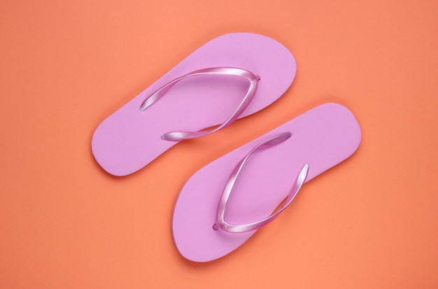 Flip-flops rosa praia na moda em fundo de papel coral. vista do topo