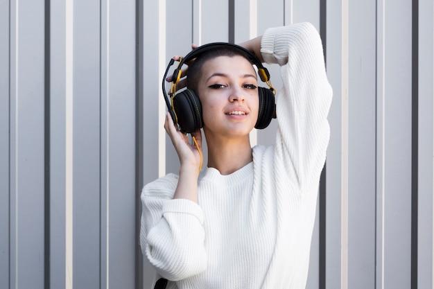 Flirty jovem fêmea com cabeça raspada usando fones de ouvido