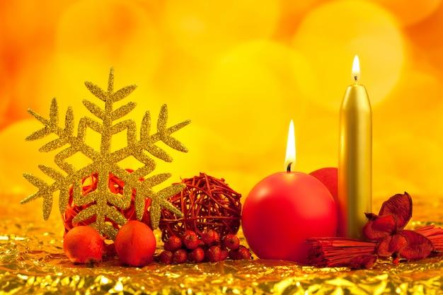 Floco de neve de natal dourado com velas vermelhas