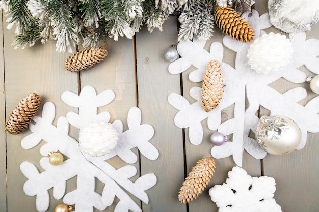 Floco de neve decorativo, árvore de natal e cone na superfície de madeira
