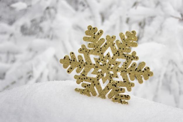 Floco de neve decorativo cintilante de superfície dourada festiva na neve real do inverno.