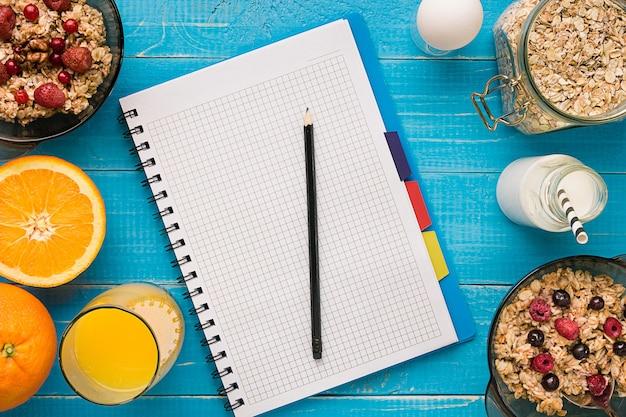 Flocos de aveia com tigela de leite e frutas com colher sobre fundo azul de madeira. alimentos saudáveis no café da manhã. vista do topo. copie o espaço