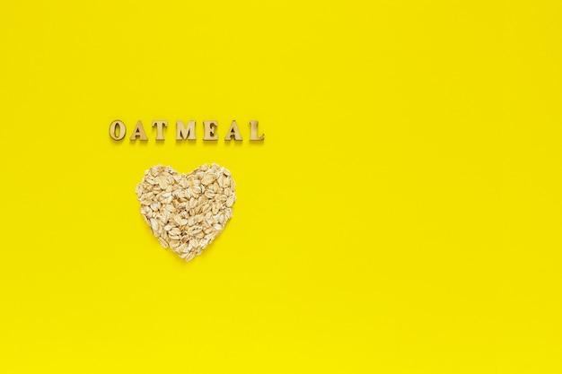 Flocos de aveia e aveia de texto no coração forma sobre fundo amarelo.