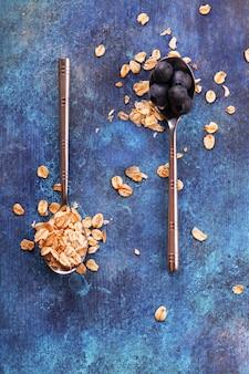 Flocos de aveia e mirtilo em colheres vintage em fundo de madeira azul grunge