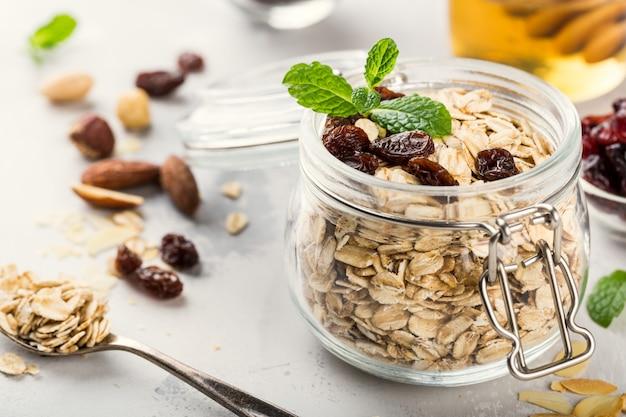 Flocos de aveia em frasco de vidro com mel, passas e nozes. conceito de pequeno-almoço saudável.