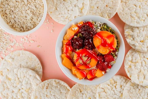 Flocos de aveia em tigelas com nozes, frutas, damasco, geléia, bolos de arroz