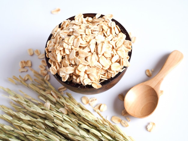 Flocos de aveia em uma tigela de madeira com espiga de arroz e colher de pau