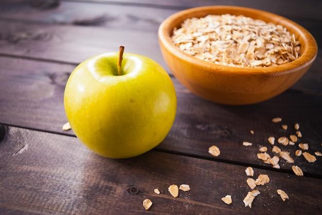 Flocos de aveia em uma tigela e uma maçã