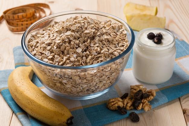 Flocos de aveia, iogurte, banana e nozes, a fita métrica fica ao lado de, o conceito de uma dieta saudável