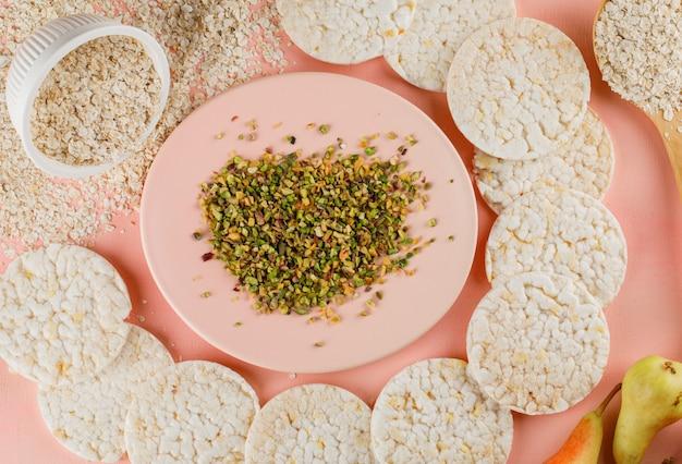 Flocos de aveia na tigela e colher de pau com bolos de arroz, pistache, peras