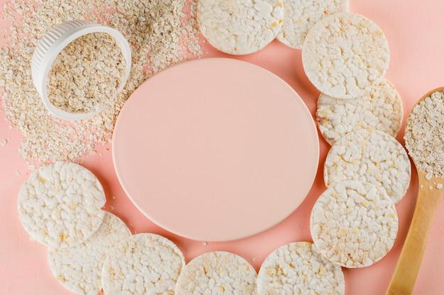 Flocos de aveia na tigela e colher de pau com bolos de arroz
