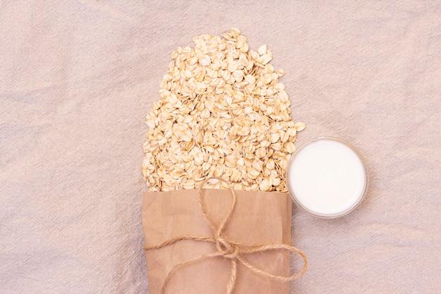 Flocos de aveia naturais secos. farinha de aveia de um saco de papel ecológico. fundo de linho natural com flocos de saco e aveia de eco. um copo de leite
