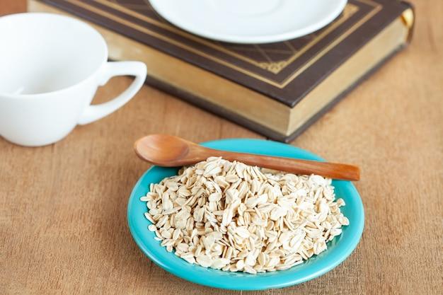 Flocos de aveia no prato na mesa de madeira