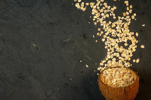 Flocos de aveia seca superior derramados de uma casca de coco no preto