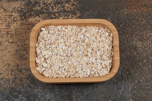 Flocos de aveia secos na placa de madeira.