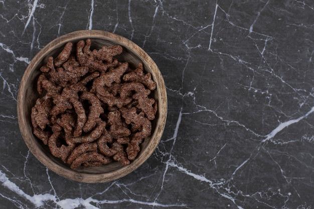 Flocos de cereais de chocolate em uma tigela de madeira.