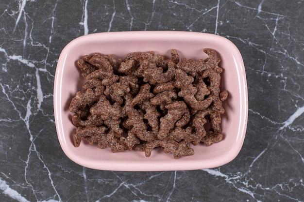 Flocos de cereais de chocolate em uma tigela rosa.