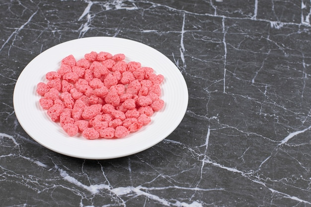 Flocos de cereais rosa na chapa branca.