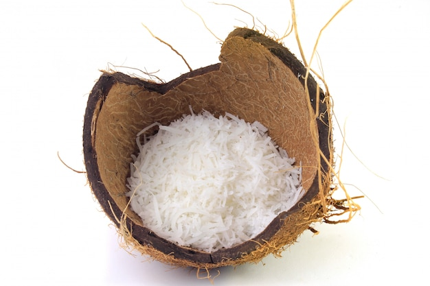 Flocos de coco frescos colocados na casca e casca isolada no fundo branco