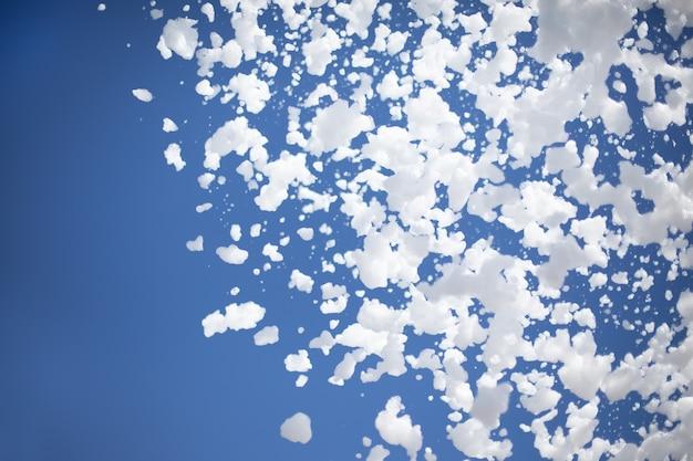 Flocos de espuma de uma festa na piscina no fundo de um céu azul e ensolarado de verão com espaço de cópia
