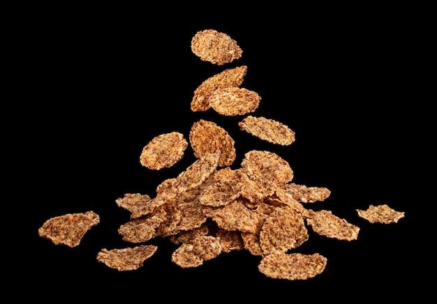 Flocos de farelo caindo em fundo preto, pilha de cereais matinais tradicionais