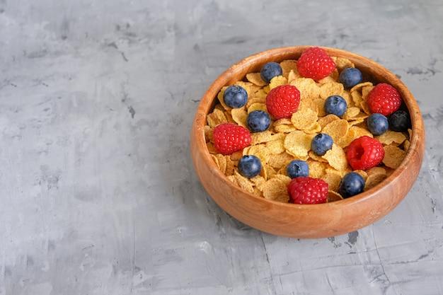 Flocos de fitness crocantes com frutas frescas. café da manhã saudável e saudável. pratos de madeira. copie o espaço.