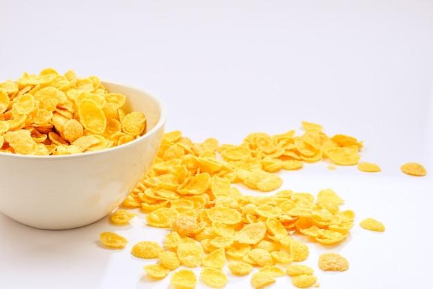 Flocos de milho caindo na tigela branca