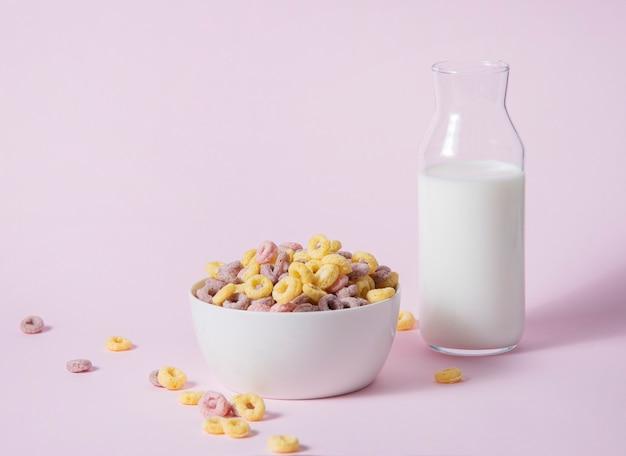 Flocos de milho coloridos doces anéis em uma tigela branca com uma garrafa de leite em um fundo rosa. vista frontal e imagem do espaço de cópia
