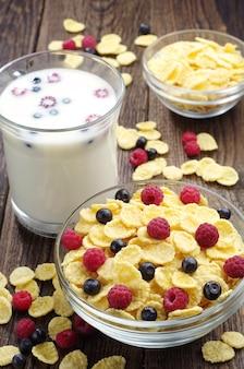 Flocos de milho com frutas e copo de leite na mesa de madeira