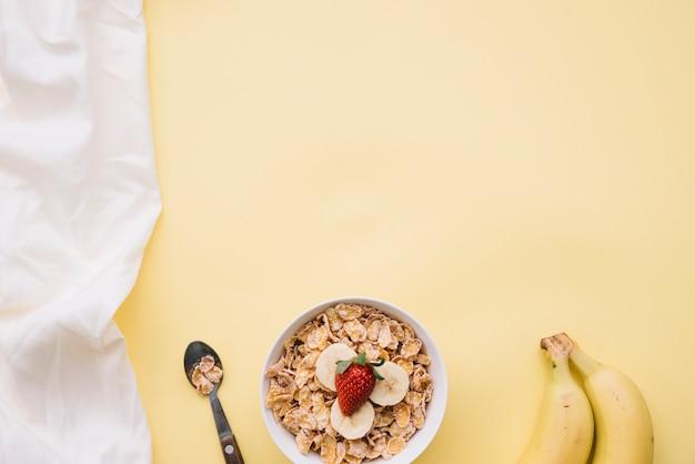 Flocos de milho com frutas na taça sobre a mesa