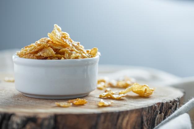 Flocos de milho com mel em uma tigela branca na superfície de madeira. copie o espaço