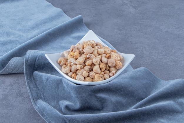 Flocos de milho com muesli em uma tigela sobre um pedaço de tecido, no fundo de mármore.