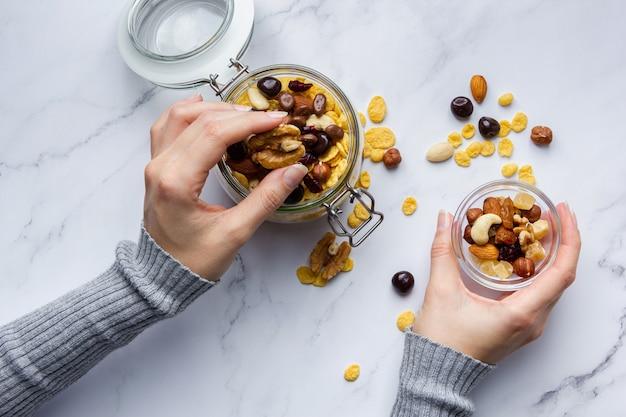Flocos de milho com nozes na jarra, realizada por mãos femininas no fundo de mármore. vista superior do café da manhã saudável.
