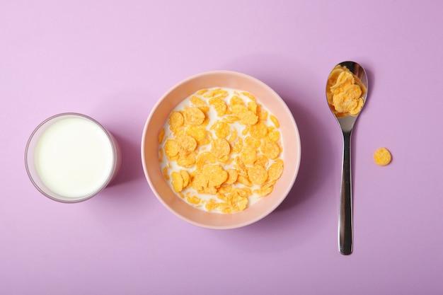 Flocos de milho crocantes com leite no café da manhã em um plano de fundo colorido