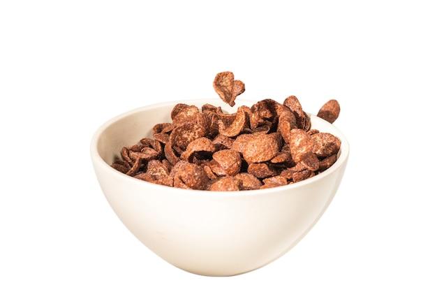 Flocos de milho de chocolate caindo para a tigela branca isolada no branco. movimento. copyspace.