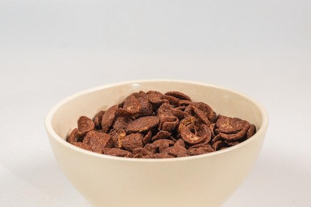 Flocos de milho de chocolate caindo para a tigela branca isolada no branco. movimento.
