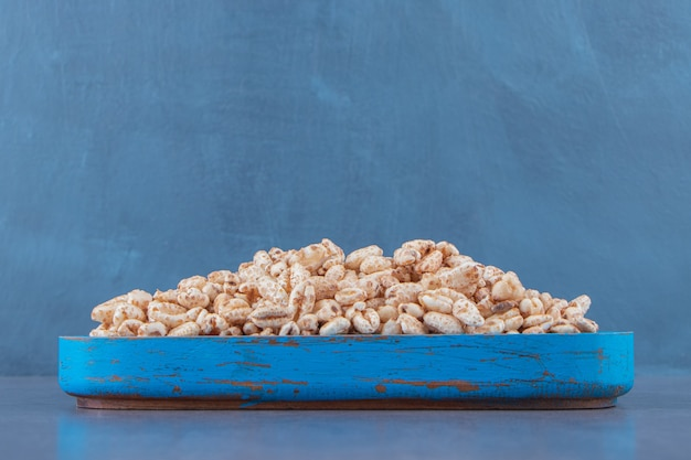 Flocos de milho doces em uma placa de madeira, na mesa de mármore.