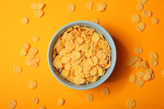 Flocos de milho dourados e crocantes em um plano de fundo colorido close-up