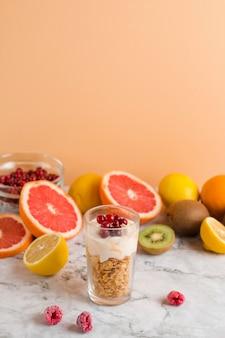 Flocos de milho e iogurte de alto ângulo em vidro com frutas