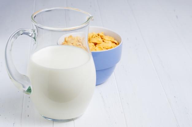 Flocos de milho e leite em uma jarra de vidro