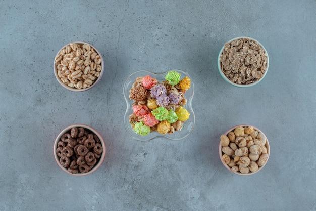 Flocos de milho em um copo de café com leite e em tigelas, sobre o fundo azul. foto de alta qualidade