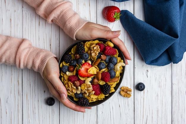 Flocos de milho em uma tigela com frutas e nozes na mesa de madeira branca. vista superior do café da manhã saudável.