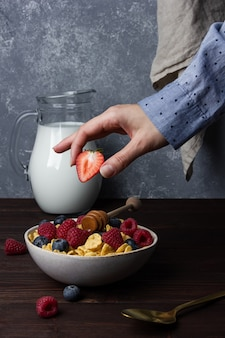 Flocos de milho em uma tigela com frutas, mel e leite na mesa de madeira. vista lateral do café da manhã saudável.