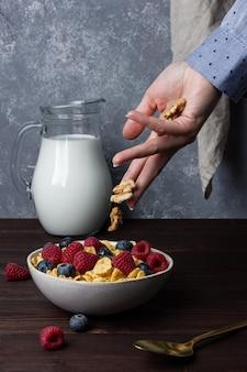 Flocos de milho em uma tigela com frutas, nozes e leite na mesa de madeira. vista lateral do café da manhã saudável.