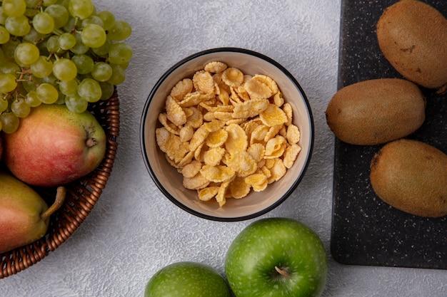 Flocos de milho em uma tigela com maçãs verdes, pera kiwi e uvas verdes em um fundo branco.