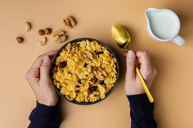 Flocos de milho em uma tigela com nozes seguradas por mãos femininas em fundo amarelo. vista superior do café da manhã saudável.