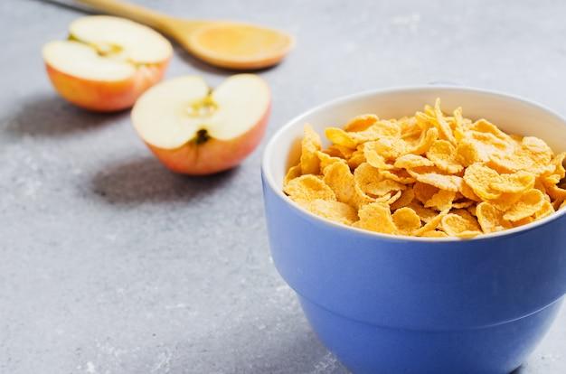 Flocos de milho em uma xícara azul e rodelas de maçã