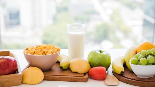 Flocos de milho; frutas; copo de leite na mesa perto da janela