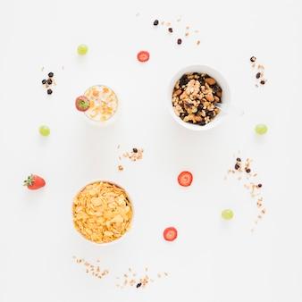 Flocos de milho; frutas secas com morango e uvas no fundo branco