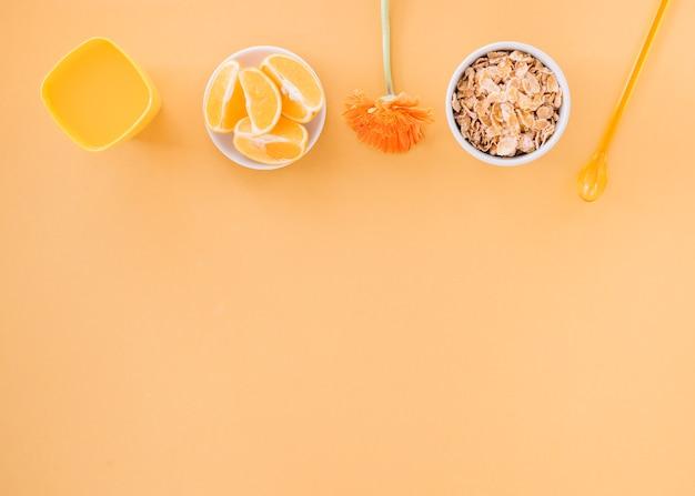 Flocos de milho na tigela com laranja e suco
